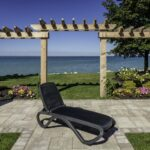 Charcoal Omega Sun Lounger in garden overlooking ocean