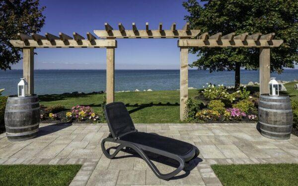 NARDI Omega Sun Lounger (Charcoal) in garden overlooking ocean