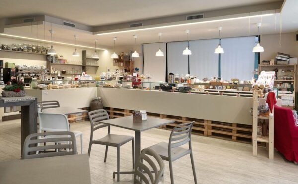 NARDI Costa Bistro Chairs in Taupe with Fiore Tables in Indoor Bakery Cafe