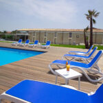 Omega-3-Piece-Sun-Lounger-Sets-lined-up-on-wooden-deck-next-to-pool