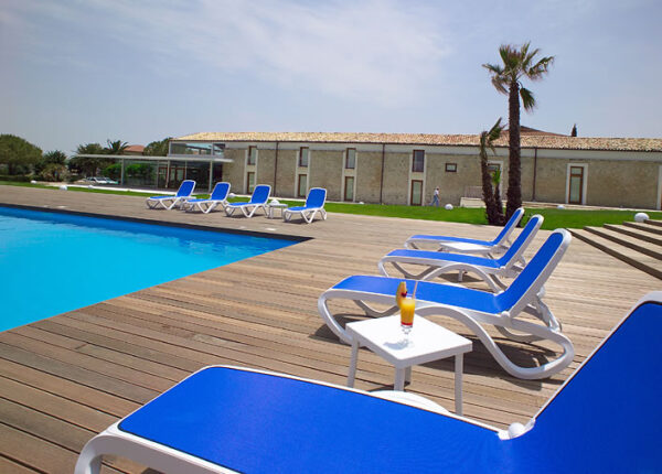 NARDI Omega 3-Piece Sun Lounger Sets lined up on wooden deck next to pool