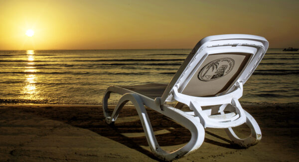 NARDI Omega Sun Lounger (White & Taupe) on beach at sunset with hotel branding