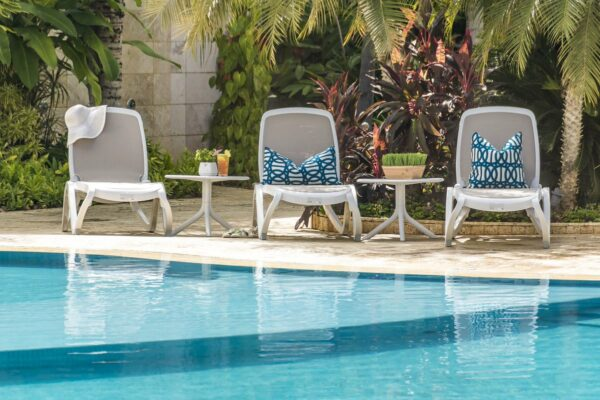 NARDI Omega Sun Loungers (White & Taupe) and Spritz Coffee Tables between pool and garden