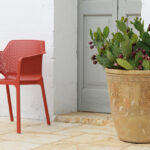 Net Chair in Coral Red with pot plant next to Mediterranean door