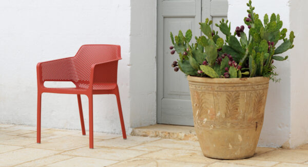 NARD Net Chair in Coral Red with pot plant next to Mediterranean door