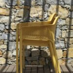 Net Chairs (Mustard Yellow) stacked on wooden deck