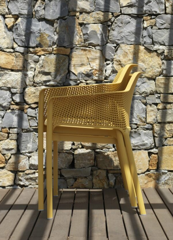 NARDI Net Chairs (Mustard Yellow) stacked on wooden deck in front of stone wall