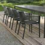 Net Chairs in Charcoal on wooden deck in outdoor dining setting with Rio Table