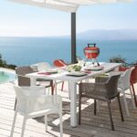 Net Chairs in White, Taupe and Coral Red around White Levante Table overlooking ocean