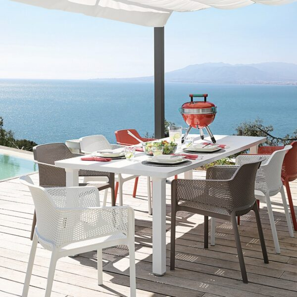 NARDI Net Chairs in White, Taupe and Coral Red around White Levante Table overlooking ocean