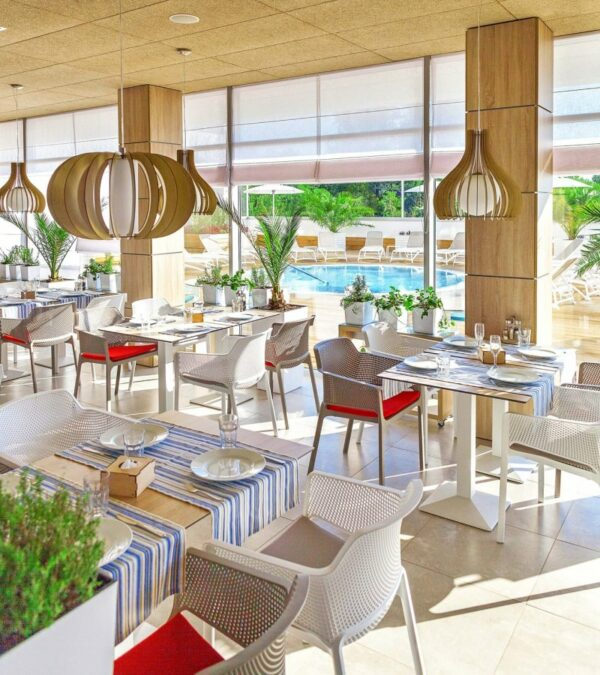 NARDI Net Chairs in White and Taupe in an indoor hotel restaurant looking out at pool and sun loungers