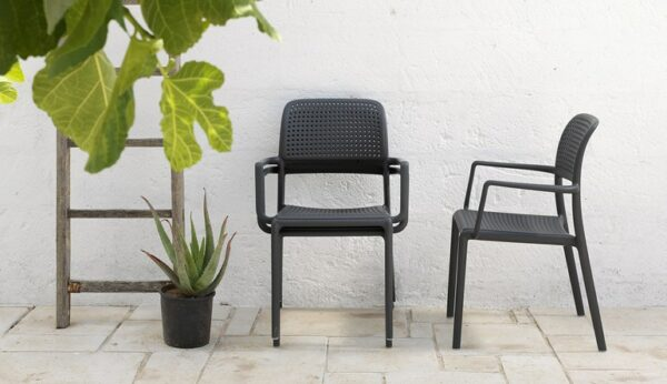 NARDI Bora Arm Chairs in Charcoal next to garden plants