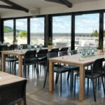 Bora Bistro Chairs in Charcoal in restaurant overlooking pier and beach
