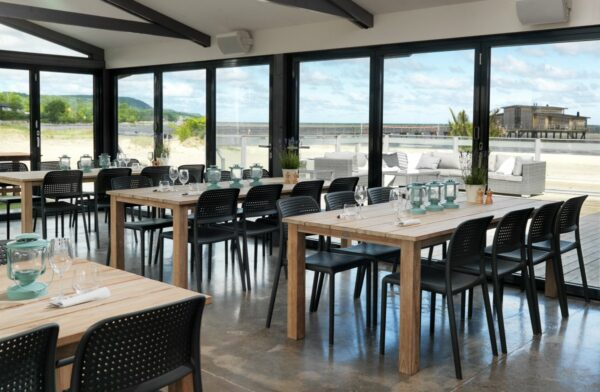 NARDI Bora Bistro Chairs in Charcoal in restaurant overlooking pier and beach