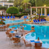 Artica Rattan Dining Chairs -Straw & Silver Legs in Hotel Poolside Setting