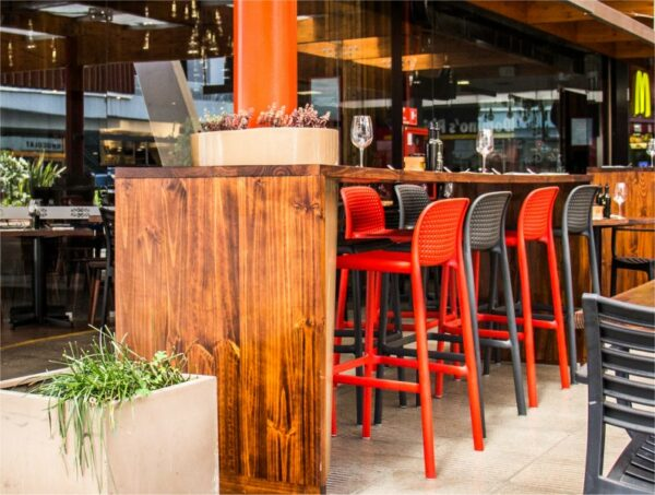 Lido Tall Outdoor Bar Stool - Charcoal & Red (Pictured in Restaurant Bar Setting)