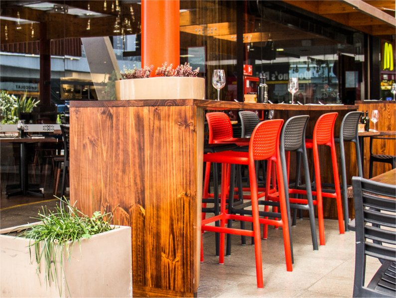 Lido Tall Outdoor Bar Stool – Charcoal & Red (Pictured in Restaurant Bar Setting)