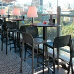 Lido Tall Outdoor Bar Stools in Charcoal and Taupe on Balcony at Restaurant