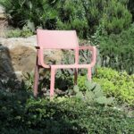 Trill Armchair (Rosa Pink) in garden with rocks and succulent plants