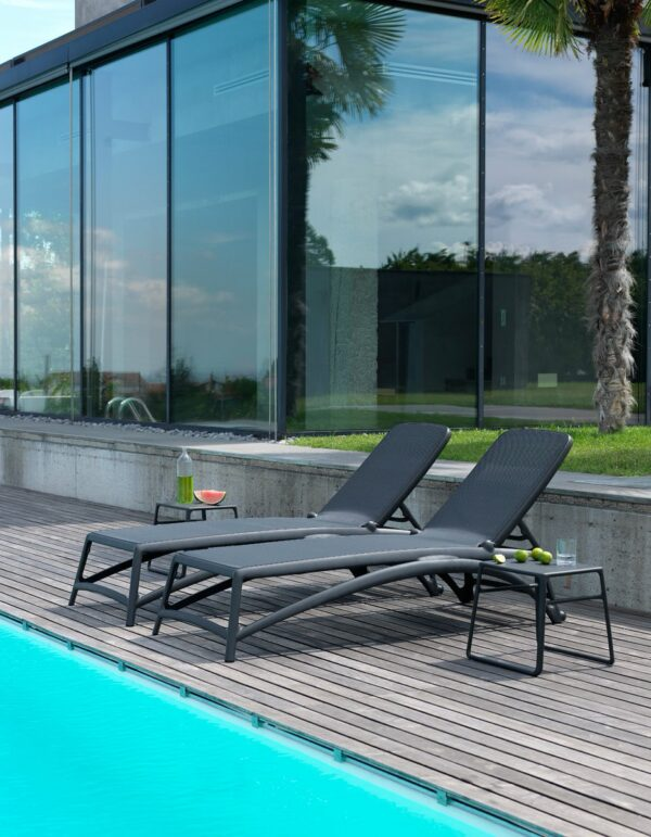 Atlantico Sun Loungers in Charcoal – Pictured on a Wooden Deck next to a Pool with Pop Side Table