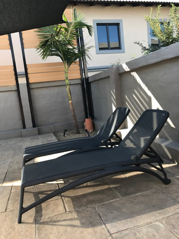 Atlantico Sun Loungers in Charcoal on Stone Tile Patio