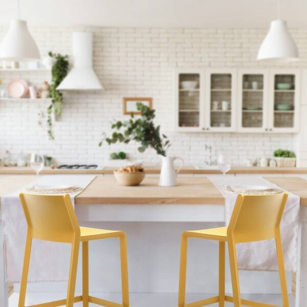 Two NARDI Trill Kitchen Counter Bar Stools in Mustard Yellow at breakfast bar in white modern farmhouse kitchen