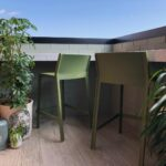 Two Trill Kitchen Counter Bar Stools Olive Green on wooden panel outdoor balcony