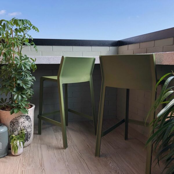 Two NARDI Trill Kitchen Counter Bar Stools in Olive Green on wooden panel outdoor balcony with pot plants