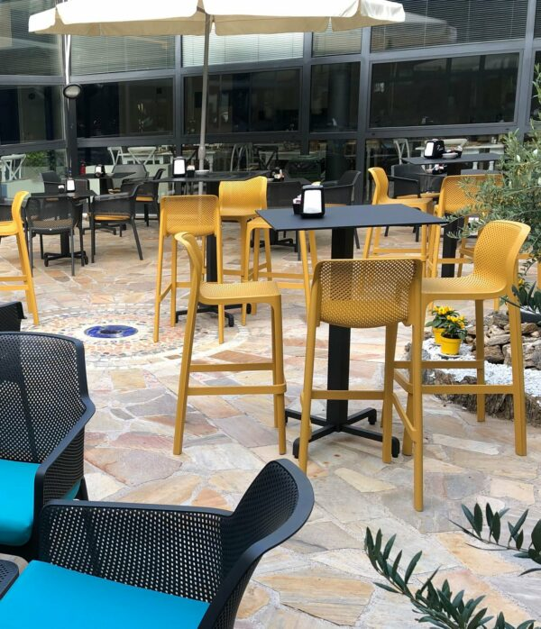 NARDI Net Tall Bar Stools around Bar Leaner in an Outdoor Café Environment in Mustard Yellow