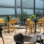 Net Tall Bar Stools in Mustard with Bar Leaners Outdoors at Cafe