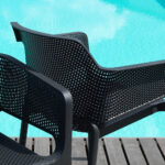 Two Net Chairs in Charcoal – Pictured on Wooden Deck next to Pool