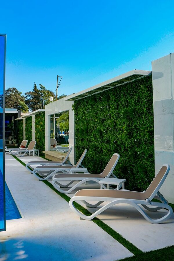 NARDI Omega 3-Piece Sun Lounger Sets (White & Taupe) next to living wall and pool