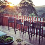 Net Kitchen Counter Stools Outdoors on Wooden Deck at Sunset